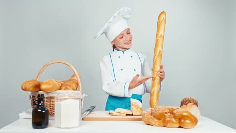 Young-Baker-Girl-Child-Holds-Long-Loaf-And-Smiling-At-Camera-Standing