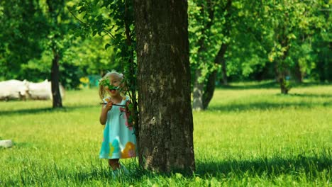 Baby-Girl-3-Years-Child-Is-Hiding-Behind-A-Tree-In-The-Park-And-Smiling