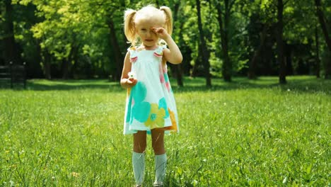 Baby-Girl-3-Years-Old-Holding-Flower-And-Standing-In-The-Park