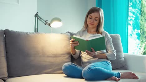 Beautiful-Young-Woman-Reading-Book-And-Smiling-At-Camera-In-Living-Room-Dolly