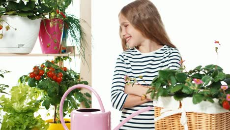 Cheerful-Blond-Girl-Watering-Plants-On-White-Background