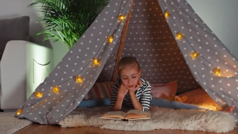 Cheerful-Child-Girl-9-Years-Old-Reading-Book-In-Wigwam-Dolly-Shot