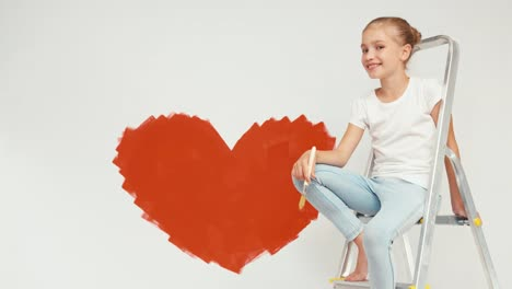 Cheerful-Child-Girl-Painted-Heart-On-The-Wall-And-Sitting-On-The-Ladder