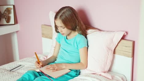 Cheerful-Child-Girl-Using-Cell-Phone-And-Writing-In-Notebook-On-The-Bed