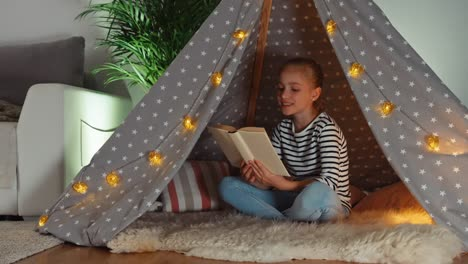 Cheerful-Child-Reading-Book-In-Wigwam-And-Smiling-At-Camera