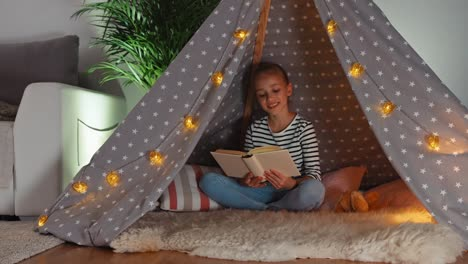 Cheerful-Child-Reading-Book-In-Wigwam-And-Smiling-Dolly-Shot