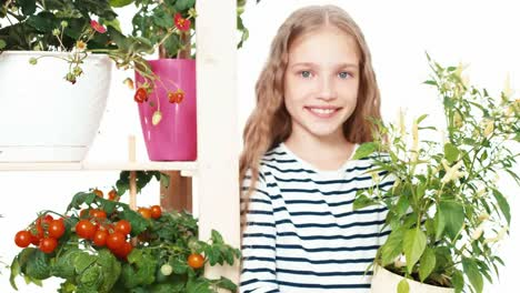 Cheerful-Girl-8-Aged-Holds-Little-Peppers-In-Pot-On-White-Background