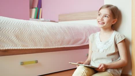 Niña-Alegre-De-9-Años-Con-Tablet-Pc-Cerca-De-La-Cama-En-El-Dormitorio