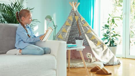 Cheerful-Girl-9-Years-Old-Reading-Book-In-Living-Room-At-Sunny-Day