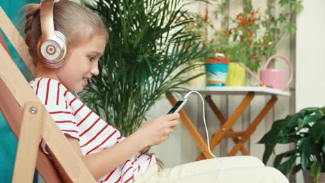 Cheerful-Girl-9-Years-Old-Using-Cell-Phone-And-Smiling-At-Camera-On-Patio
