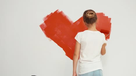 Cheerful-Girl-9-Years-Painting-Red-Heart-On-The-Wall