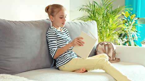 Cheerful-Girl-9-Years-Sit-Up-On-The-Sofa-And-Take-A-Book-Dolly-Shot