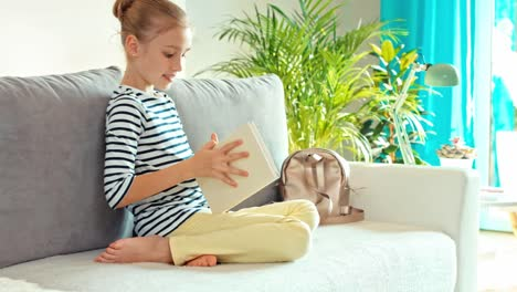 Cheerful-Girl-9-Years-Sit-Up-On-The-Sofa-With-Book-Dolly-Shot