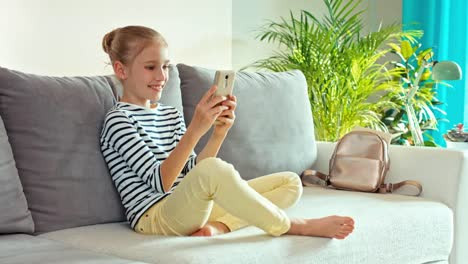 Cheerful-Girl-9-Years-Sitting-On-The-Sofa-With-A-Cell-Phone-And-Smiling
