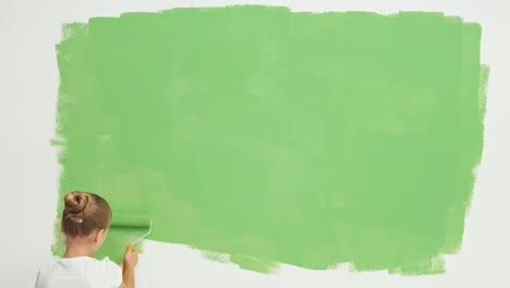 Cheerful-Girl-Child-Painting-Wall-To-Green-Color