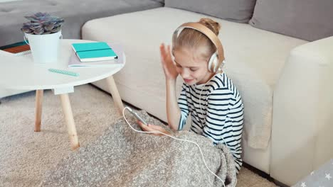 Cheerful-Girl-Listening-Music-In-Headphones-From-Cell-Phone-Top-View