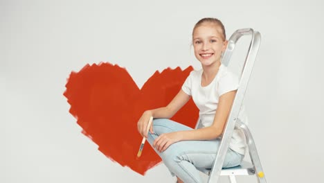 Cheerful-Girl-Painted-Heart-On-The-Wall-And-Smiling-At-Camera