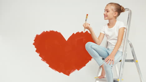 Cheerful-Girl-Painted-Red-Heart-On-The-Wall-And-Sitting-On-Ladder-And-Smiling