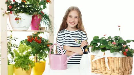 Cheerful-Girl-Standing-Near-Her-Vegetables-In-Pots-On-White-Background