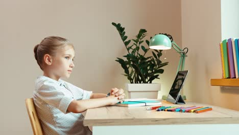 Cheerful-School-Girl-9-Aged-Sitting-At-The-Desk-And-Smiling-At-Camera