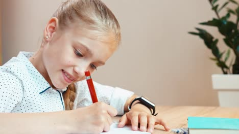 Cheerful-School-Girl-Writing-In-Notebook-Using-Pen-Panning-Shot