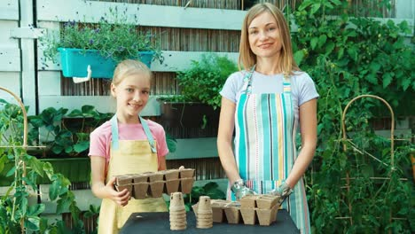 Child-8-Aged-Holding-Peat-Pot-Mother-And-Daughter-Planning-Seeds