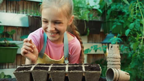 Child-8-Aged-Planting-White-Seed-In-Soil-Into-A-Peat-Pot-Little-Farmer-Smiling