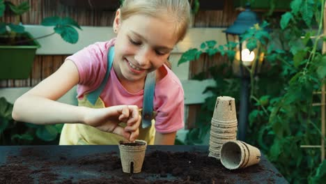 Child-8-Aged-Planting-White-Seed-Into-A-Peat-Pot-Cheerful-Little-Farmer