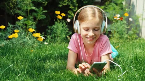Child-9-Aged-In-Headphones-Lying-On-The-Garden