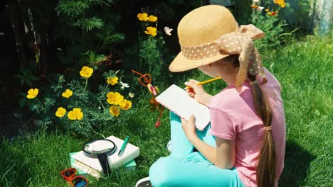 Child-Aged-8-Writing-In-Notebook-And-Sitting-On-The-Grass-In-The-Garden