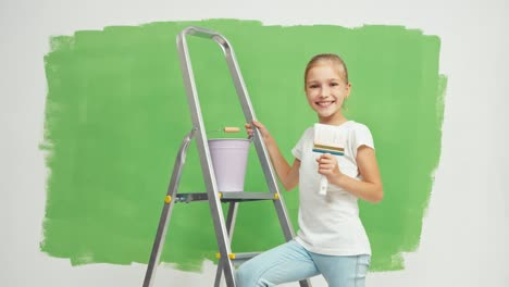Child-Enters-To-Scene-With-Paint-Brush-In-Her-Hand-And-Smiling-At-Camera