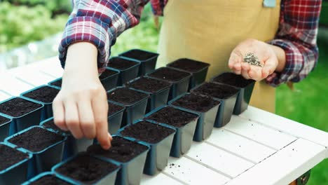 Niño-Niña-De-8-Años-Plantar-Semillas-De-Verduras-A-Macetas-De-Plástico-Con-Tierra-Closeup