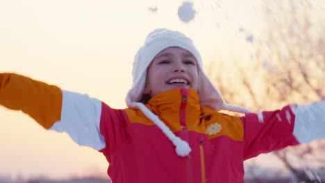 Child-Girl-8-Years-Old-Playing-With-Snowflakes-Outdoors-And-Spinning-In-Sunset