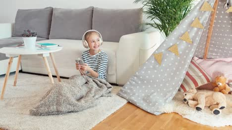 Child-Girl-9-Years-Old-Listening-Music-In-Headphones-From-Cell-Phone-Sitting