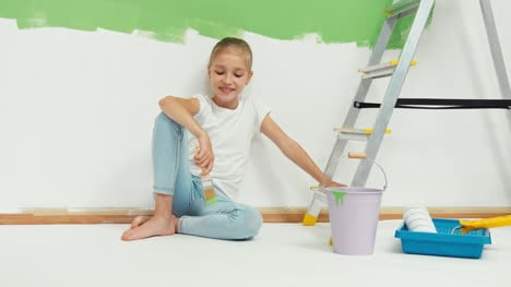 Child-Girl-9-Years-Old-Sitting-On-Floor-Near-Wall-Holds-Paint-Brush-And-Smiling