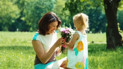 Child-Giving-Flowers-To-Mother-Portrait-Family-Mother-And-Daughter-Sitting