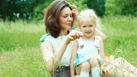 Close-Up-Portrait-Mother-And-Daughter-Playing-With-Ladybird-In-The-Park