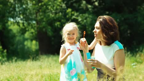 Close-Up-Portrait-Mother-And-Daughter-Playing-With-Soap-Bubble-In-The-Park