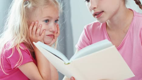 Close-Up-Portrait-Older-Sister-Reading-Book-In-The-Bedroom