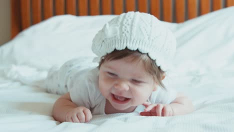 Closeup-Portrait-Newborn-Baby-Lying-On-The-Bed-And-Smiling-At-Camera-Newborn