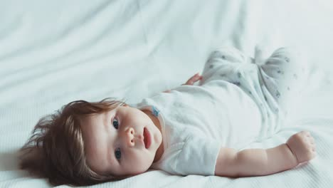 Happy-Newborn-Baby-Boy-Girl-Lying-On-The-Bed-And-Looking-At-The-Camera