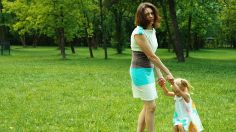 Mother-Spinning-Baby-Girl-3-Years-Old-In-The-Park