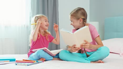 Older-Sister-Reading-Book-To-Her-Younger-Sister-And-They-Laughing