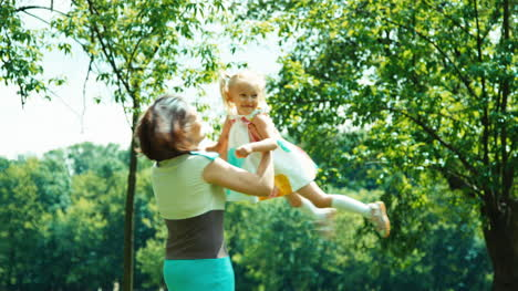 Portrait-Family-Mother-Spinning-Daughter-In-The-Park