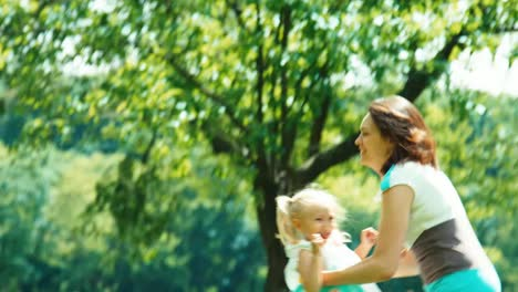 Portrait-Family-Mother-Throwing-In-The-Sky-Baby-Up-In-The-Park