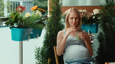 Portrait-Pregnant-Woman-Drinking-Kiwi-Juice-And-Sitting-On-The-Balcony