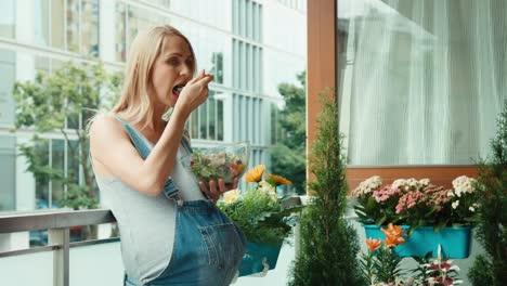 Mujer-Embarazada-Comiendo-Ensalada-Y-De-Pie-En-El-Balcón