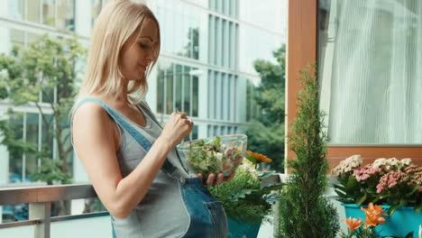 Mujer-Embarazada-Con-Cabello-Rubio-Comiendo-Ensalada-Y-De-Pie-En-El-Balcón