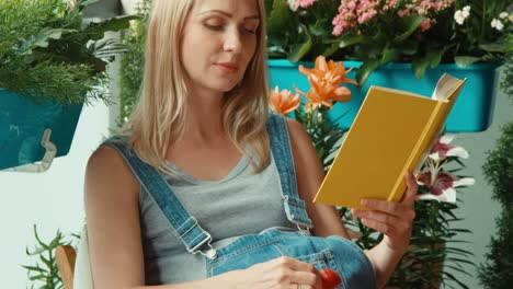 Pregnant-woman-rubs-her-belly-and-reads-a-book-in-the-garden