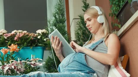 Pregnant-Woman-With-Blonde-Hair-Using-Tablet-PC-And-Listening-Music